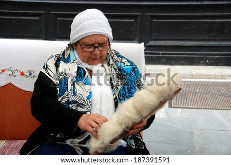 LJUBLJANA, SLOVENIA - APRIL 12, 2014: Bosnian woman hand spins at Festival of Bosnian Food and Presentation of Bosnian Rug organized by Women's Association Zemzem on Stritar street in old town.