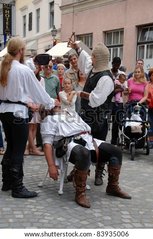 LJUBLJANA, SLOVENIA - AUGUST 28: Medieval fair in Ljubljana, Slovenia, on August 28, 2011.  Demonstration of lifestyle in medieval time. Dentist shows the extracted tooth. Patient fainted away.
