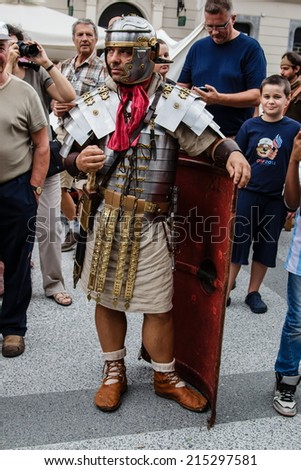 "LJUBLJANA, SLOVENIA - AUGUST 24th 2014: Ancient Roman legionnaire standing, leaning on his shield on the Ljubljana street on a summer afternoon as a part of ""Ave Emona"" event. - stock photo"