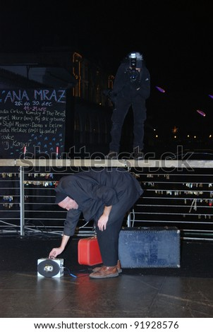LJUBLJANA, SLOVENIA - DECEMBER 26: Clown, magician, mime Daniel Warr from Germany at traditional street festival Ana Mraz in Ljubljana, SI, on December 26, 2011. Man takes photographs from the fence.