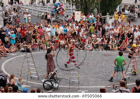 "LJUBLJANA, SLOVENIA - JULY 3: An unidentified man performs at the street circus "" Chat'Pitre Compagnie"" at the traditional street theater festival ""Ana Desetnica"" on July 3, 2010 in Ljubljana, Slovenia. The group is from France and Croatia. - stock photo"