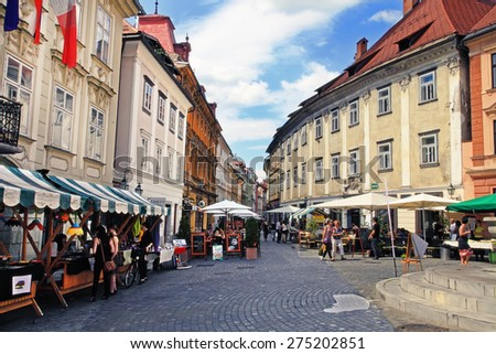 LJUBLJANA, SLOVENIA -  JUNE 28, 2014: Street in the old city center of Ljubljana with street shops and cafes. LJUBLJANA, JUNE 28, 2014.