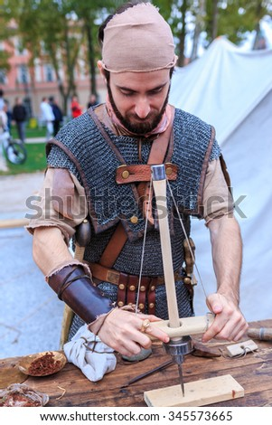 "LJUBLJANA, SLOVENIA - SEPTEMBER 26h 2014: Ancient Roman legionnaire making a fire on the Kongres square in Ljubljana on a summer afternoon as a part of ""Ave Emona"" event"