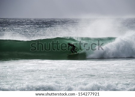 LLANDUDNO, SOUTH AFRICA - FEBRUARY 05: Surfing a barrel. February 5th 2011. Llandudno Beach is one of the Cape's most beautiful beaches, surrounded by large granite boulders,overlooked by mountains. - stock photo