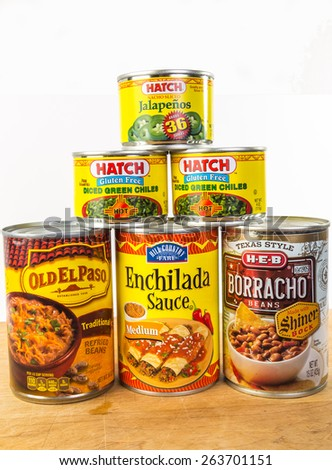 LLANO, TEX-MAR 24, 2015:  Cans of Mexican  Food on white background with copy space.  Enchilada; refried beans; borracho beans; chile peppers; jalapenos; spices and sauces. - stock photo