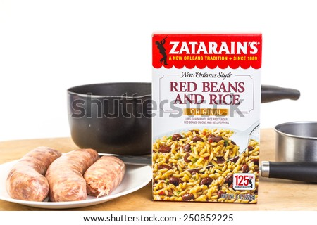 LLANO, TEXAS-FEB 06, 2015: Zatarain's New Orleans Style Red Beans and Rice in a box ready for sauce pan and measured amount of water.   Add Sausage and Eat.  Kitchen utensils against white background. - stock photo