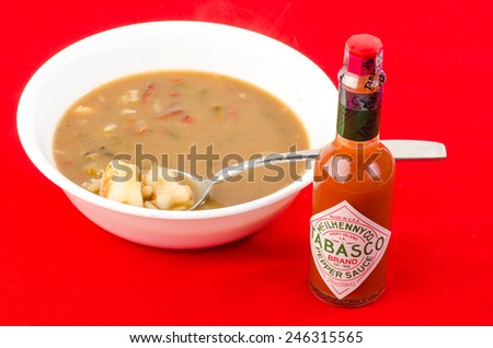 LLANO, TEXAS-JAN 22:  Bottle of McIlhenny Tabasco Pepper Sauce on bright red tablecloth with bowl of seafood gumbo in background. - stock photo