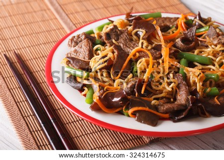 Lo mein with beef, muer and vegetables close-up on a plate. horizontal
