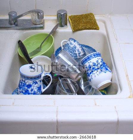 Load of dirty dishes in kitchen sink