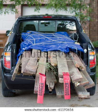 "load of lumber demolition debris in the bed of a pickup truck. Shallow depth of field with selective focus on the ""danger"" flags on the back of the load. - stock photo"