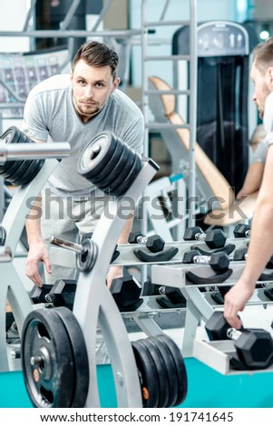 Load on the biceps of dumbbells. Successful athlete working out with dumbbells and looking forward in the mirror in the gym. Side id athlete. - stock photo