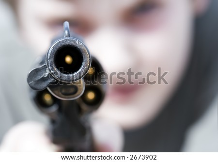 Loaded gun aimed at you, focus on gun barrel (shallow dof) - stock photo