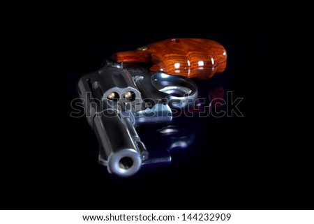 Loaded hand gun made of blue steel on black background. - stock photo