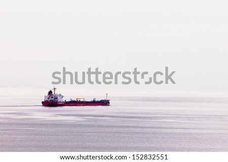 Loaded oil tanker ship heading out on calm ocean to transport and supply petroleum based fossil energy overseas - stock photo