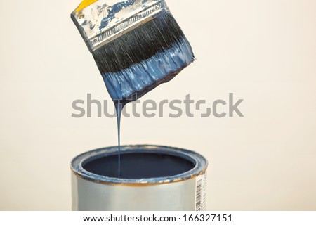 Loaded Paintbrush after dipping it into bucket. - stock photo
