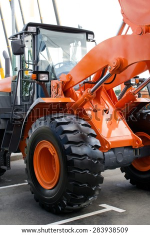 Loader excavator construction machinery equipment staying on the road. Fragment of machine - stock photo