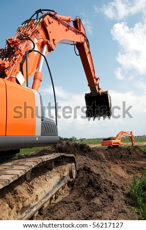 Loader Excavator doing construction works standing in field with risen bucket outdoors - stock photo