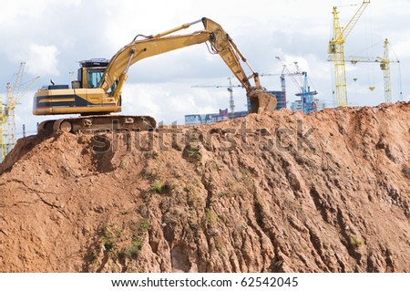 loader excavator in open sand mine over construction site