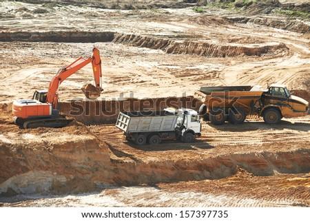 loader excavator machine loading dumper truck at sand quarry - stock photo