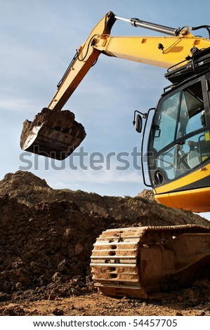 Loader Excavator standing in quarry with risen bucket over cloudscape sky - stock photo