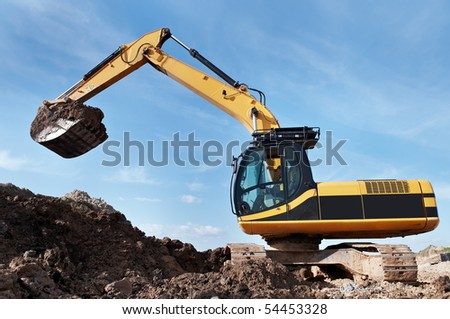 Loader Excavator standing in sandpit with risen bucket over cloudscape sky - stock photo