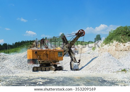 Loader excavator standing near mountains of rubble, in summer day on background of blue sky - stock photo