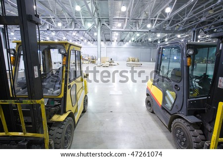 Loader in  large modern storehouse - stock photo