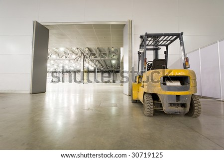 Loader in modern storehouse near gate - stock photo