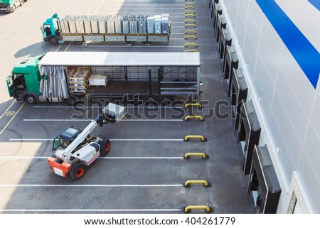 Loader loads the goods in the cargo truck, top view - stock photo