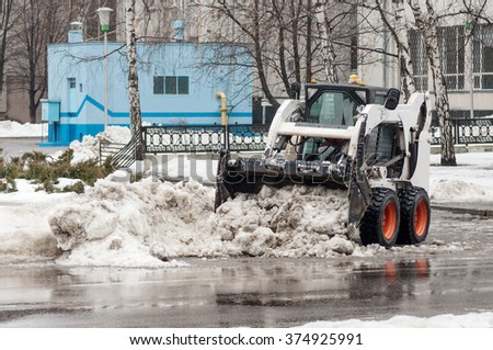 loader removes snow on city streets - stock photo