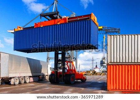 Loading and unloading of containers crane truck and special truck in the port on a sunny day - stock photo