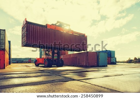 Loading and unloading of containers in the port on a bright sunny day - stock photo