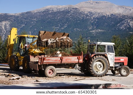Loading Construction rubble on tractor cargo cart, Taurus Mountains in the background, Turkey