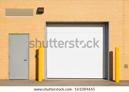 Loading dock with a  white gate and a smaller grey door - stock photo