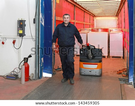 Loading goods in truck with pallet jack - stock photo
