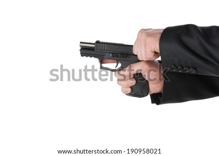Loading gun. Close-up of man in suit loading gun while isolated on white