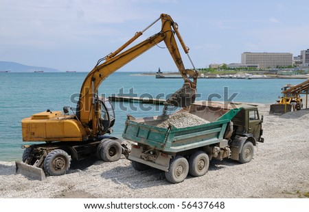 Loading of a pebble by a dredge in a dumper - stock photo