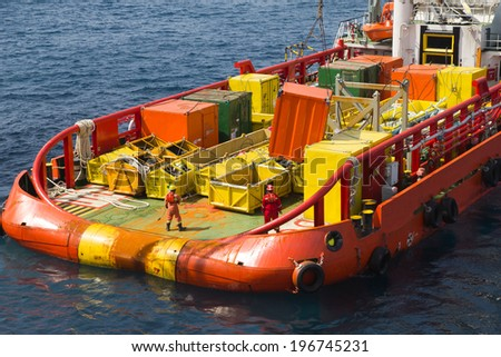 Loading of cargo on deck of a supply vessel - stock photo