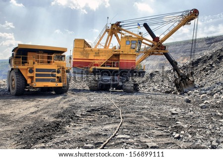 Loading of iron ore on very big dump-body truck HDR - stock photo