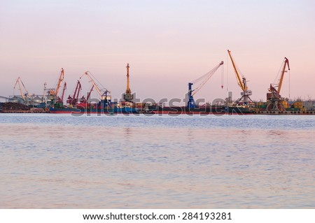 Loading of scrap metal in the river port at sunset - stock photo