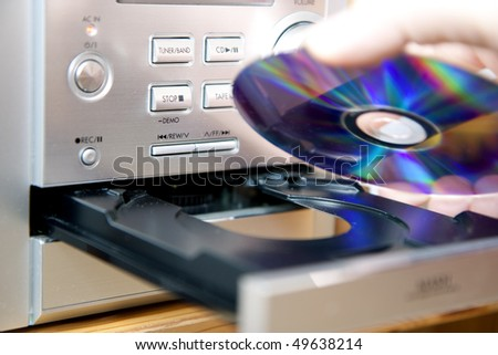Loading or putting CD medium into player - stock photo