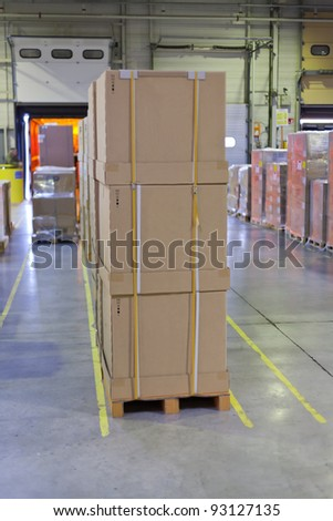 loading palleted carton boxes in storage warehouse in track - stock photo