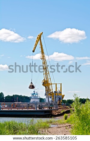 Loading sand with the help of a yellow crane on a barge. River White, Russia - stock photo