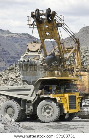 Loading the iron ore into heavy dump truck at the opencast mining - stock photo