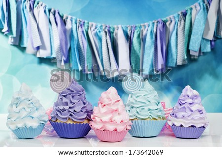 loads of cupcakes in pink aqua and purple - stock photo