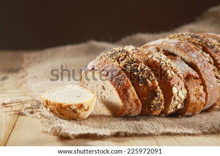 Loaf of assorted crusty fresh bread artistically arranged in slices on hessian on a rustic wooden table - stock photo