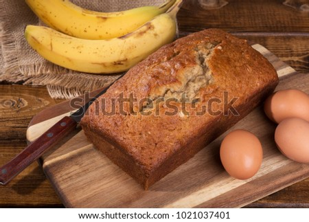 Loaf of banana nut bread with the ingredients of brown eggs and bananas on the side