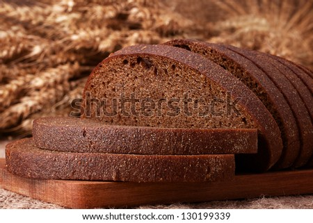 Loaf of bread and rye ears still life on rustic background - stock photo