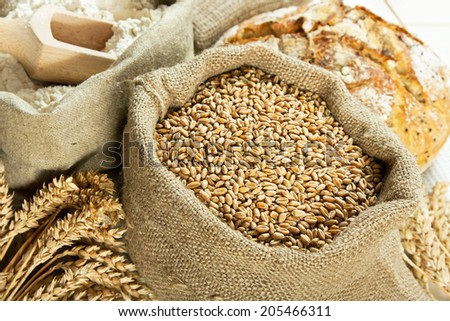 Loaf of bread, flour, wheat grain and wheat spike on table - stock photo