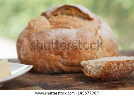 loaf of bread on cutting board. piece of bread with bite taken from it. - stock photo
